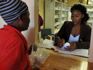 Sanelisiwe Mthembu providing pharmaceutical instructions to a patient over a counter